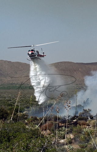Firefighting helicopter dropping water